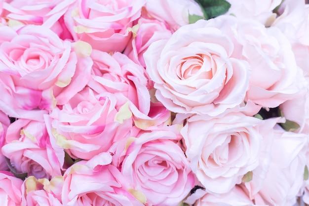 バレンタインデーのコンセプトとして、背景がぼやけた多くの生地の淡いピンクのバラのクローズアップ。