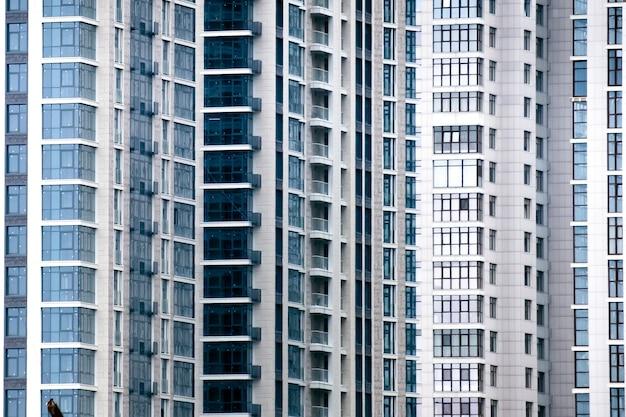 新しいアパートのファサードの多くの窓のクローズアップ。背景について。
