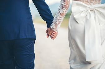 Крупным планом семейная пара, держась за руки в день свадьбы