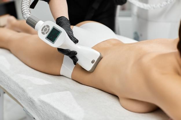 Крупный план руки массажиста, массирующей спину женщины с помощью устройства для сжиженного газа