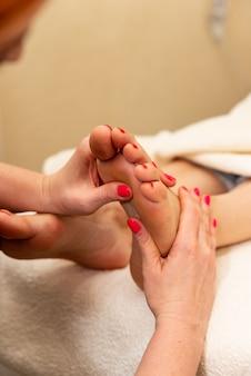 스파에서 여성에게 발 반사 요법을 하는 안마사의 클로즈업. 웰빙 센터에서 발 마사지를 하는 치료사 손. 건강 스파에서 발 마사지를 받는 여자.