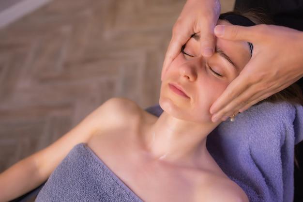 Крупным планом руки массажистки массируя женское лицо женщина закрыла глаза с удовольствием