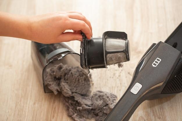 手の掃除機のひどく詰まった、汚れたフィルター、掃除機のほこりや粉のクローズアップ、家庭用コンセプト