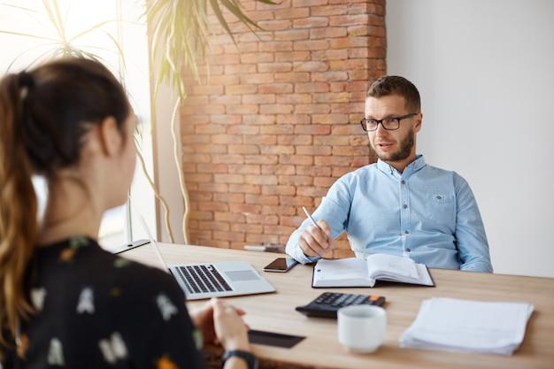 Закройте вверх зрелого бородатого директора компании в стеклах сидя в офисе с темноволосой девушкой перед им на собеседовании для приема на работу. мужчина спрашивает женщин об опыте работы