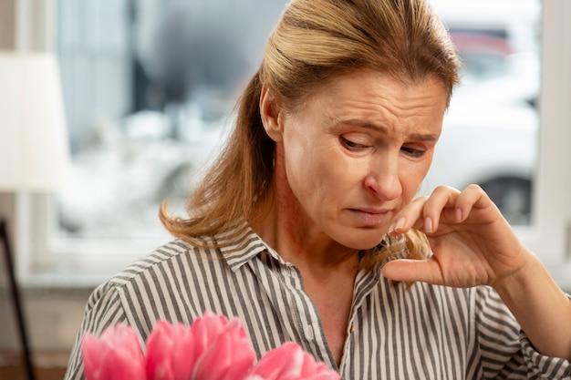 花に気分が悪く、アレルギーを感じている成熟したブロンドの髪の妻のクローズアップ