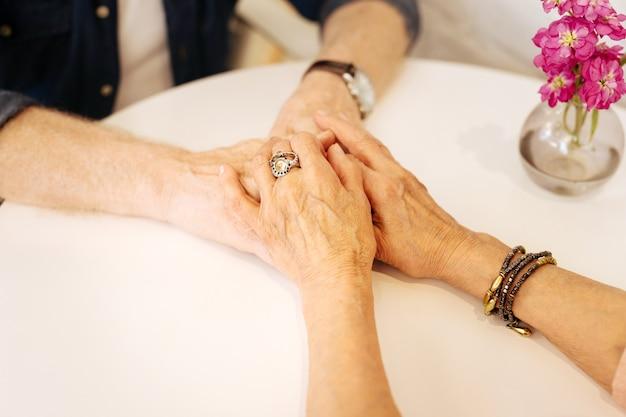 Крупный план зрелых женских и мужских рук, держащих друг друга и находящихся на белой поверхности