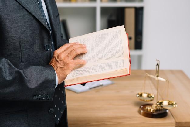 Крупный план зрелого адвоката чтение книги закона в зале суда