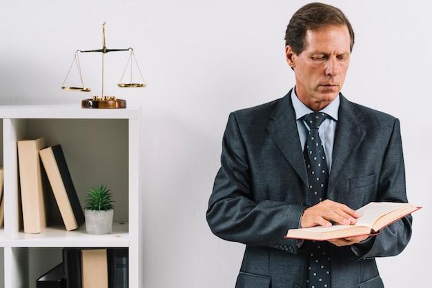 Крупный план зрелого адвоката чтение книги закона в офисе