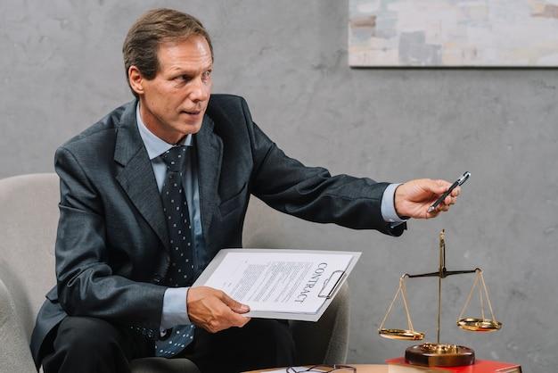 Крупный план зрелого мужчины советник, проведение контракта в руке, давая ручку