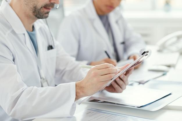 성숙한 남성 의사의 근접 테이블에 앉아 그의 동료와 함께 의료 양식을 작성