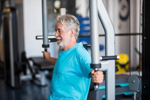 体を鍛え、体を鍛えるために体重を持ち上げるだけで運動をしているジムの成熟した男性のクローズアップ-アクティブな年金受給者のシニアトレーニングを一生懸命トレーニングし、ジムのマシンを保持しています