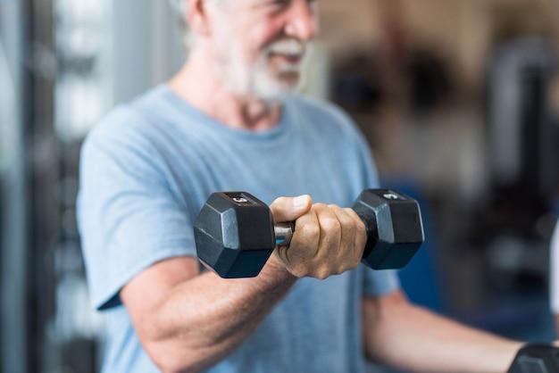健康とフィットネスのためにジムで運動をしている2つのダンベルを持っている成熟した男性のクローズアップ-アクティブなシニアリフティングウェイトの肖像画