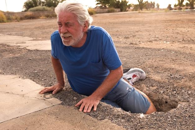 通りの穴に落ちたばかりの成熟した男のクローズアップ-一人で助けを必要としている先輩が通りの仕事に落ちた