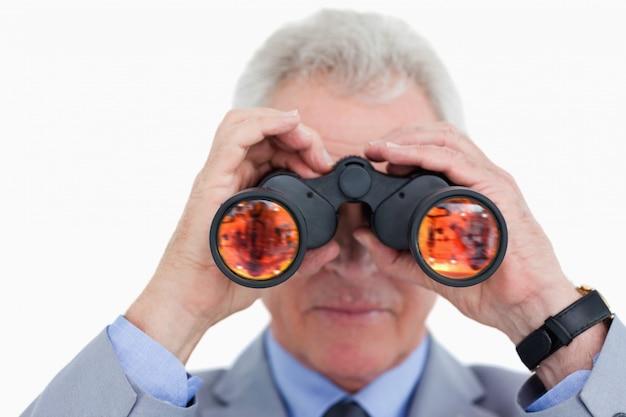 Закройте зрелого торговца, просматривающего шпионское стекло