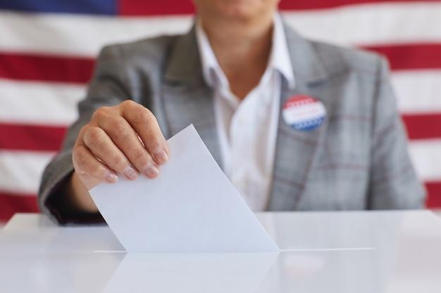 Крупный план зрелой женщины, помещающей бюллетень голосования в урну для голосования, стоя против американского флага в день выборов, скопируйте пространство