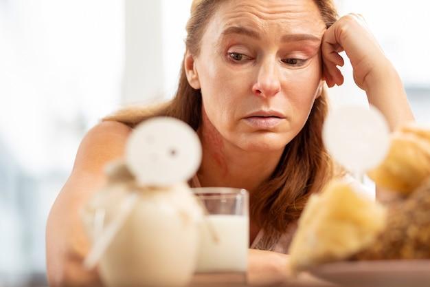 ペストリーや乳製品に食物アレルギーを持つ顔のしわを持つ成熟した女性のクローズアップ