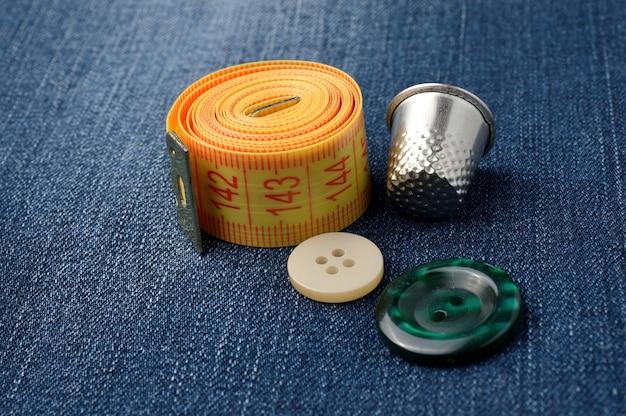 ボタンと指ぬきの巻尺のクローズアップ。