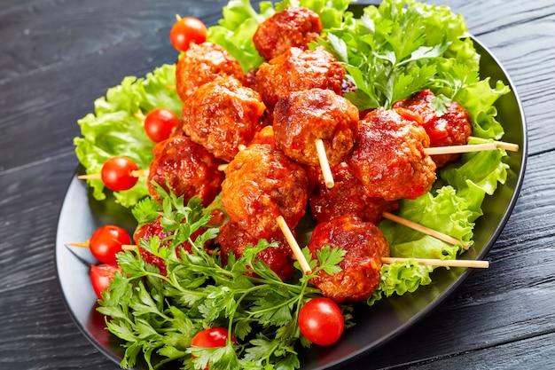 Крупный план фрикаделек на шпажках со свежими помидорами на ложе из зелени на черной тарелке, уличная еда, горизонтальный вид сверху