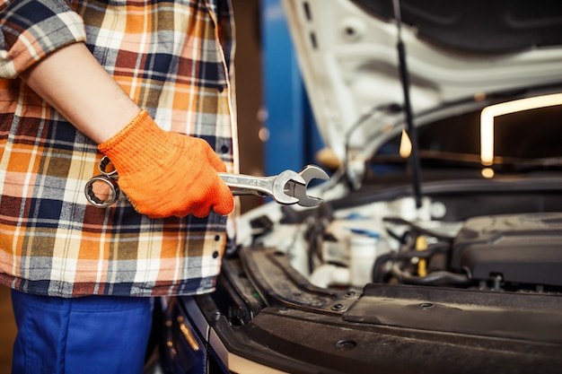 車のエンジンを操作し、レンチを保持している整備士のクローズアップ