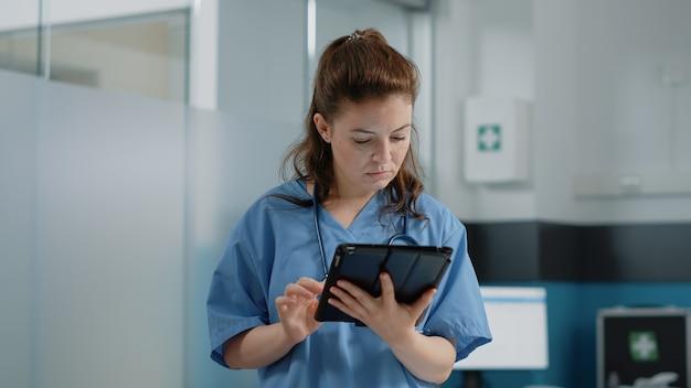 情報とタブレット画面を見ている医療助手のクローズアップ
