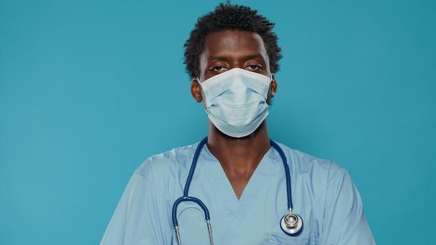 카메라를 보고 얼굴 마스크와 의료 조수의 클로즈업