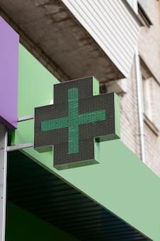 약국 건물, 약국 및 약리학 개념에 대한 의료 십자가의 클로즈업