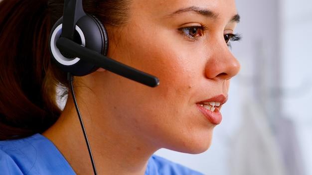 病院での遠隔医療の話し合い中に、ヘッドホンで患者に相談している医療従事者のクローズアップ。医療制服を着た医療医師、予約を手伝うドクターナースアシスタント