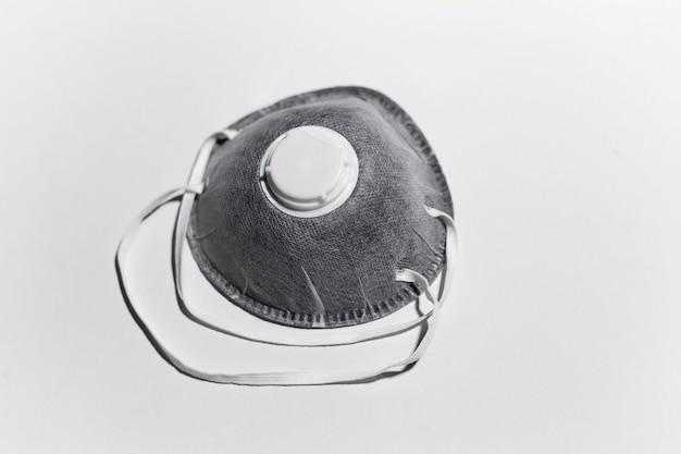 白い壁に、医療用保護インフルエンザマスク、色のスライバーのクローズアップ。