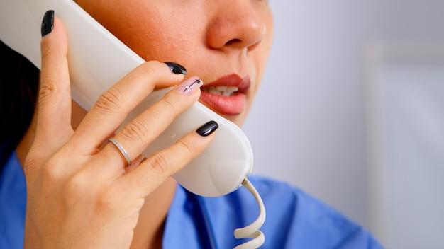 予約をしている病院の患者からの電話に応答する医療受付係のクローズアップ。医療制服を着た医療医師、遠隔医療コミュニケーションを支援する医師助手