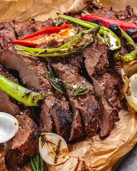 Крупным планом средне приготовленный стейк с чесноком луком красным и перцем чили на пергаментной бумаге
