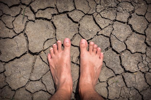 乾燥したひびの入った地球のテクスチャの男性の足のクローズアップ