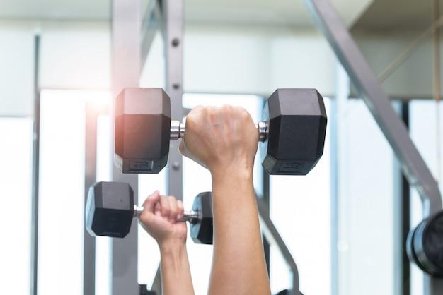 男性の手のクローズアップは、ダンベルを持ち上げることによって運動しています。フィットネスルームで