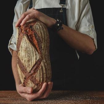 木製のテーブルの黒い背景に全粒穀物から焼きたてのライ麦パンを保持している男性の手のクローズアップ