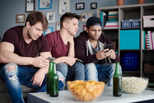 거실에 스마트폰을 들고 있는 남자들 클로즈업