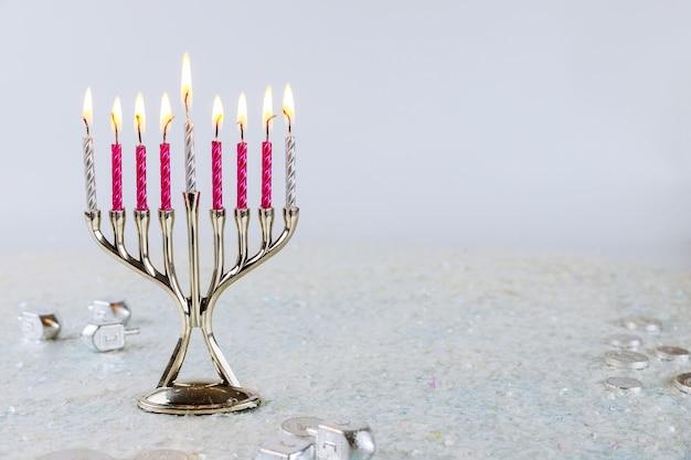 白い背景の上のハヌカのキャンドルで本枝の燭台のクローズアップ。ユダヤ教の祝日の概念。