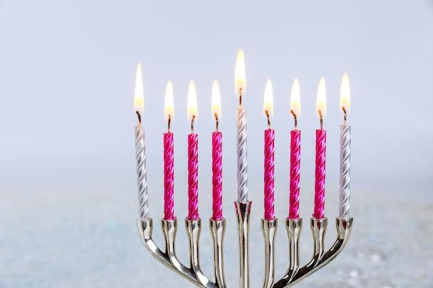 白い背景の上のハヌカのキャンドルで本枝の燭台のクローズアップ。ユダヤ教の祝日。