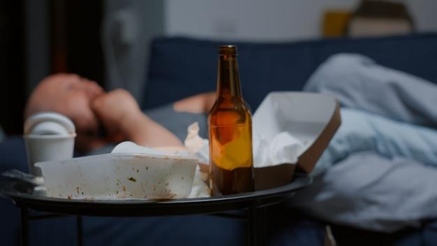 バックグラウンドで必死に泣いている落ち込んでいる男と乱雑なテーブルのクローズアップ