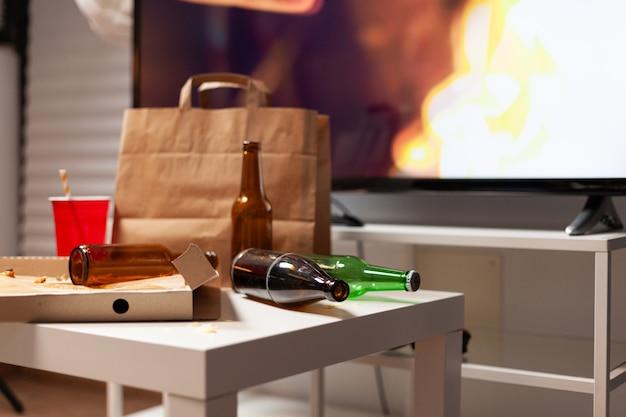 ゴミの食べ物と残り物の酒で乱雑なテーブルのクローズアップ