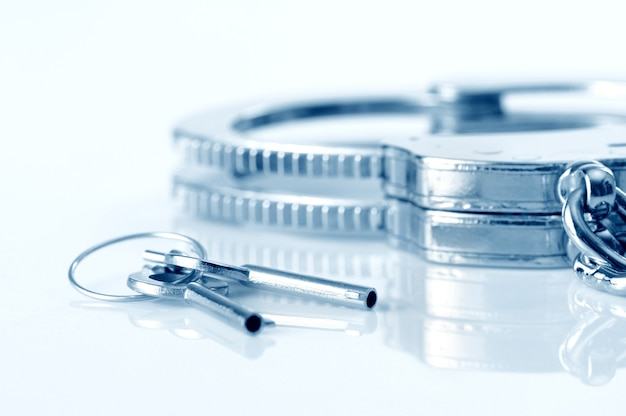 白い背景の上に分離された金属製の手錠と鍵のクローズアップ。性的なゲームとbdsmの概念の練習