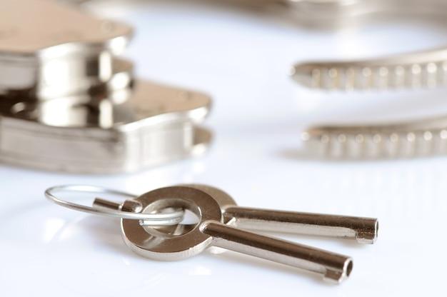 白い表面上に分離された金属製の手錠と鍵のクローズアップ。性的なゲームとbdsmの概念の練習