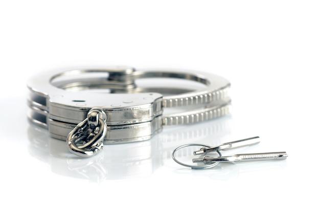 Крупный план металлических наручников и ключей, изолированных на белой поверхности. сексуальные игры и практика концепции бдсм