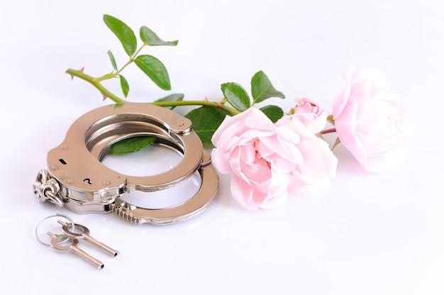 金属製の手錠、鍵、白い背景の上に分離されたロマンチックなピンクの花のクローズアップ。性的なゲームとbdsmの概念の練習