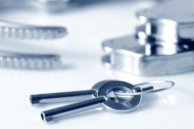 白い表面上に分離された手錠への金属製の鍵のクローズアップ。性的なゲームとbdsmの概念の練習