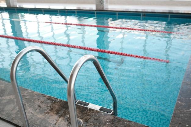 헬스 클럽의 수영장 입장에 사용되는 난간이있는 금속 수영장 계단의 근접