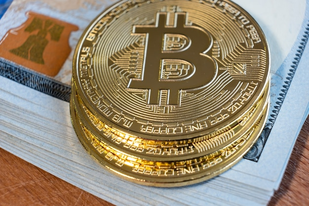 Закройте металлических блестящих монет криптовалюты bitcoin на долларовых банкнотах. концепция электронных децентрализованных денег.