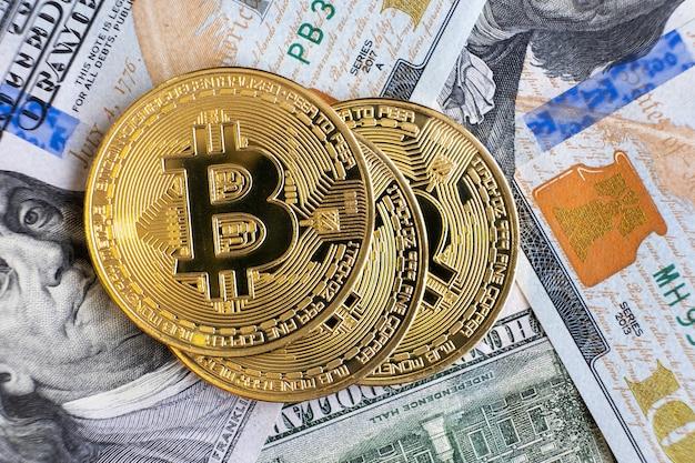 미국 달러 지폐에 반짝이는 금속성 비트코인 암호 화폐 동전을 닫습니다. 전자 분산 화폐 개념입니다.