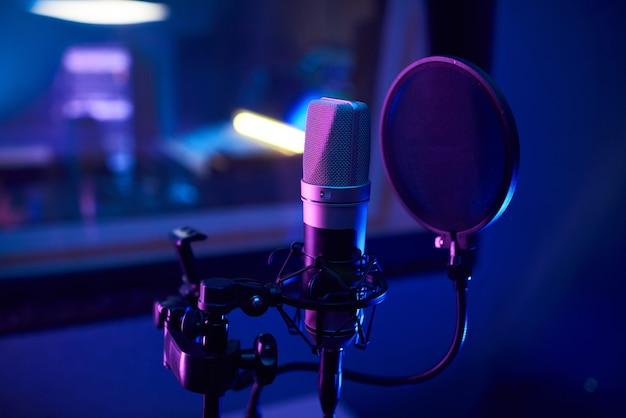 曲を録音するためにレコーディングルームに立っているマイクのクローズアップ