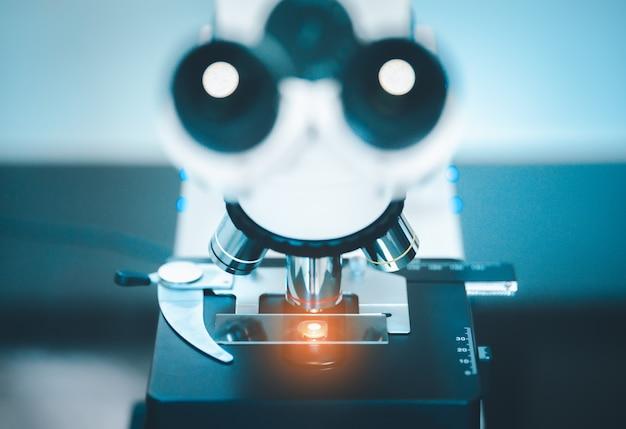 Закройте микроскоп с тестовым образцом в медицинской исследовательской лаборатории или научной лаборатории.