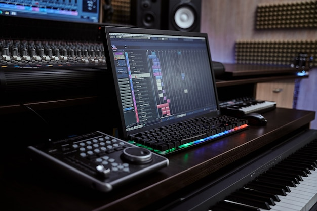Крупным планом миди-синтезатор с экранной клавиатурой для создания музыки