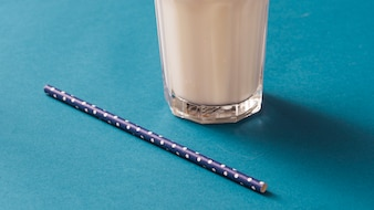 Close-up of milk glass with polka dot drinking straw on blue backdrop